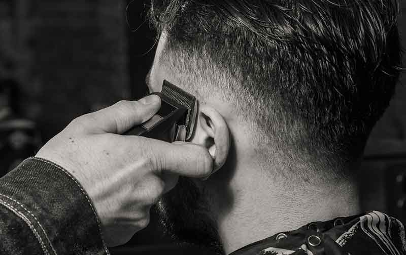 Barber using clippers at a Wheaton barber shop