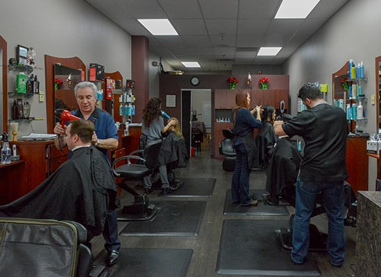 Inside Golden Scissors Barber Shop with hairstylists cutting customers hair